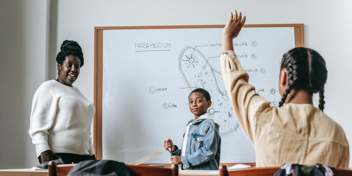 black woman and students during lesson